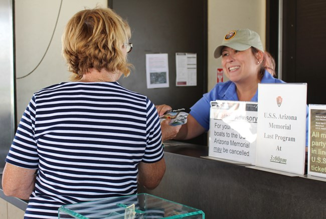 Volunteer Ann Marie assists a visitor at the Pearl Harbor Visitor Center ticket counter.