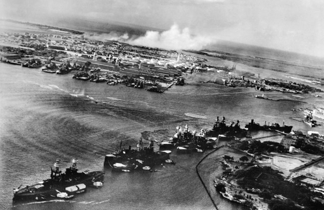 A black and white aerial photo of the line up of battleships, called Battleship Row, at the start of the Pearl Harbor attack.