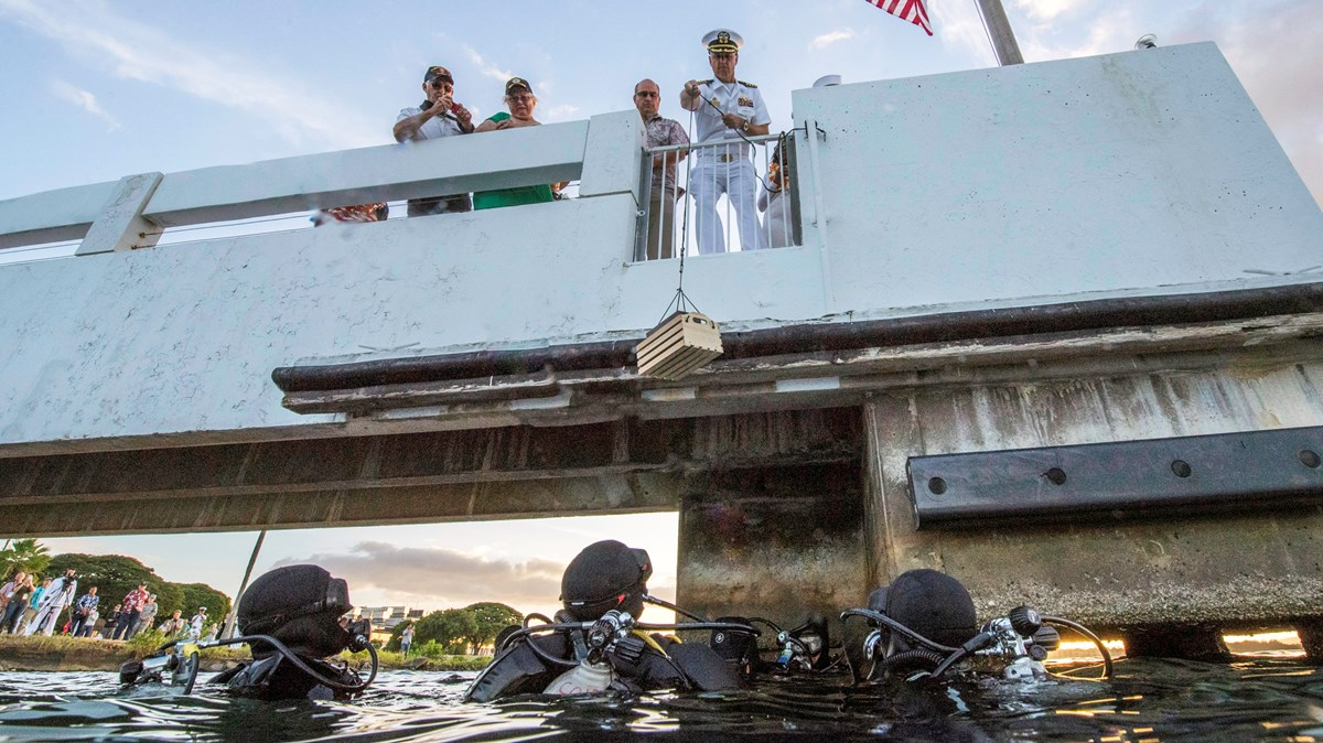 Three National Park Service divers in the water reach up for the urn of USS Utah crewmember Harry Hohstadt during his interment ceremony on December 6, 2017.