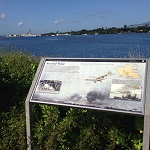 An interpretive exhibit along the water's edge, with the USS Arizona Memorial in the distance.