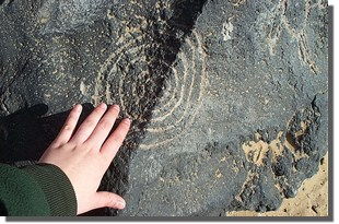 Persons hand touching a petroglyph