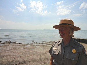 Park Ranger in uniform standing on a beach with Lake Erie in the background.