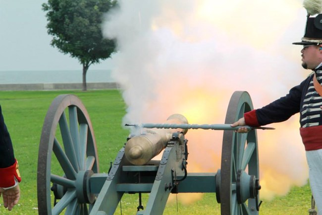 Reenactor stands on the right side of cannon on a field carriage and lights the cannon. Smoke & fire come out the muzzle of the cannon.