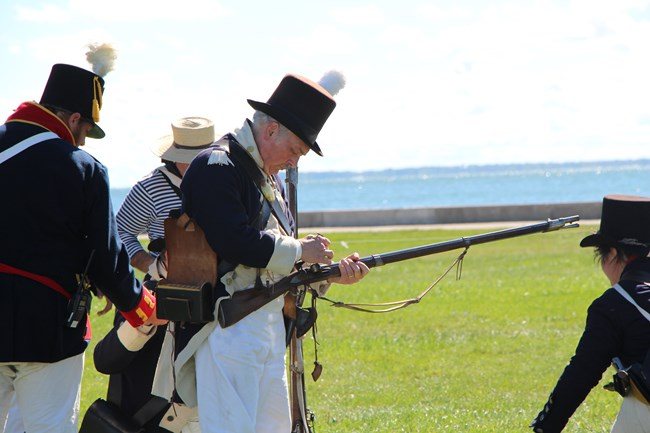 A reenactor prepares his musket for a demonstration.