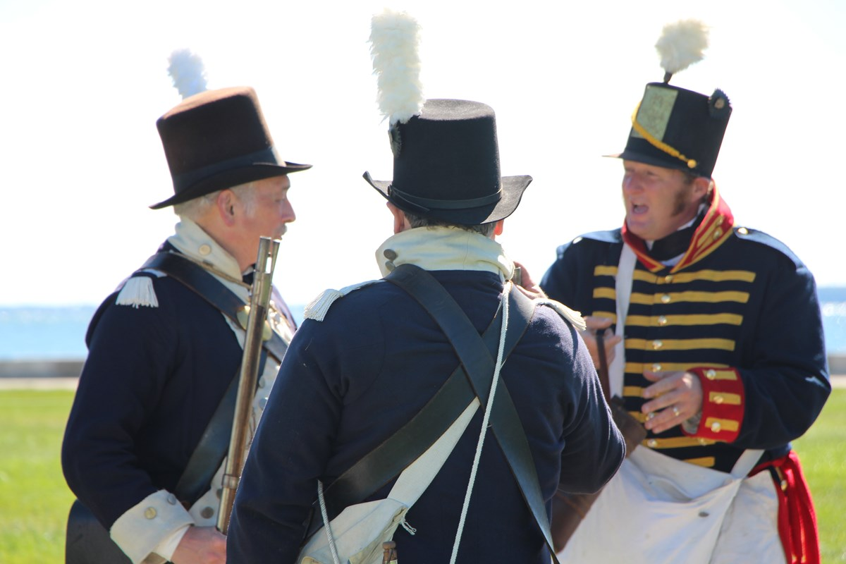 Three reenactors, circled together, confer before a demonstration.