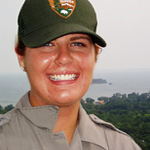 Park Ranger on observation deck with lake and islands in background.