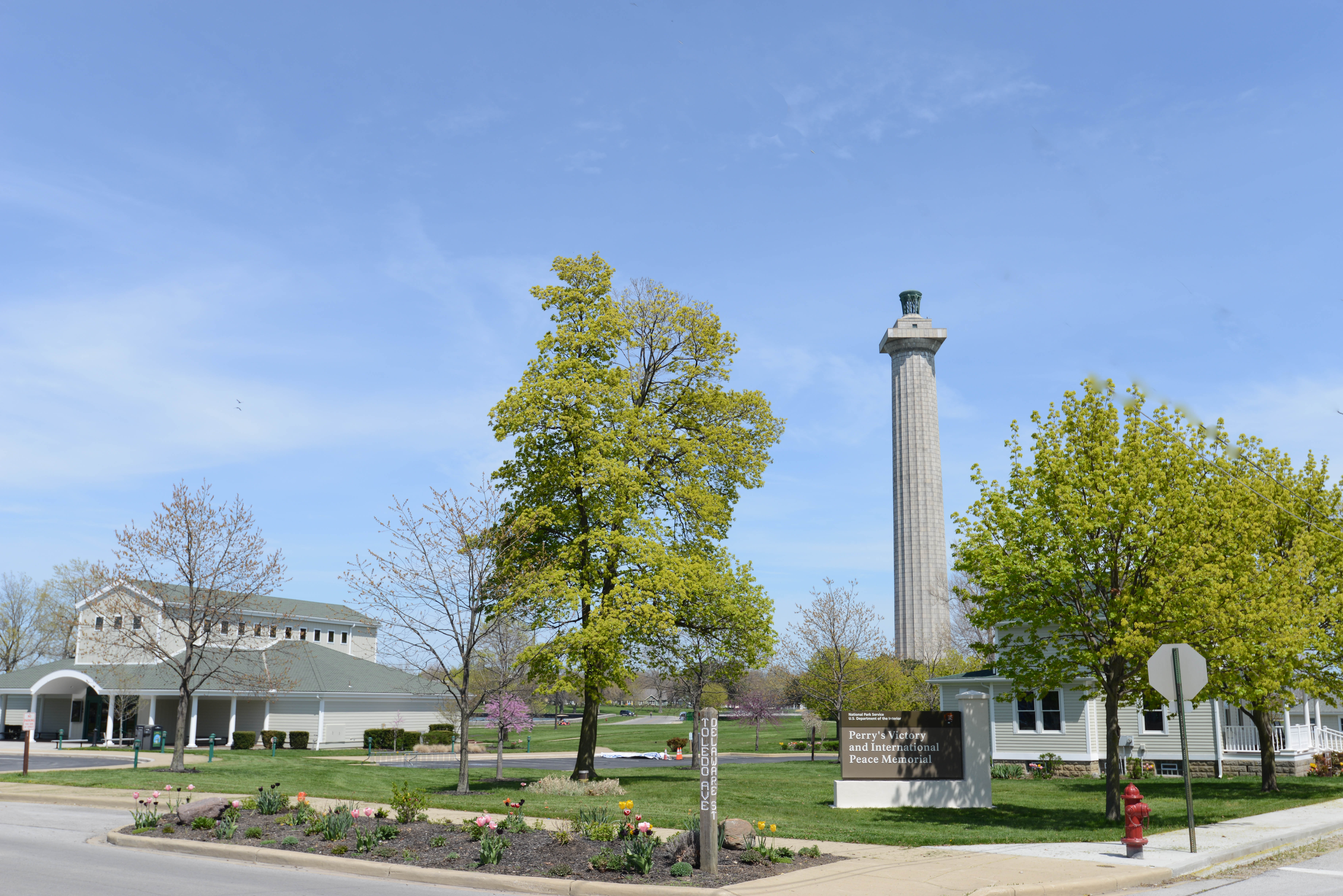Memorial column in background, Visitor Center to the side, and park sign in foreground
