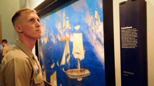 Man in tan military uniform looking at a painting of the Battle of Lake Erie.