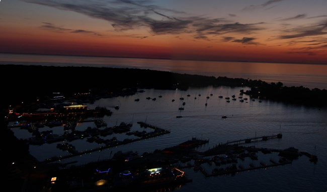 Sunset over Lake Erie with the lights of Put-in-Bay coming on and boats in the harbor.