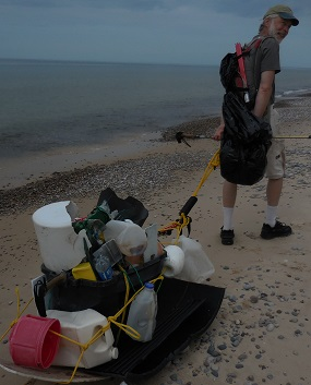 Volunteer pulling sled of trash collected from beach