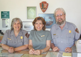 Judy, Ronnie, and Brody at the Grand Sable Visitor Center counter.