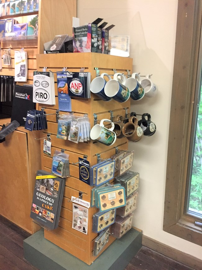 Sales Items at Munising Falls VC include mugs, pins, patches and tokens