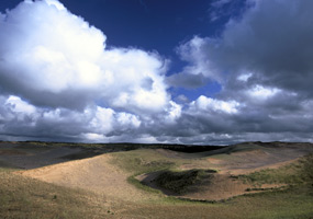 Brilliant white clouds and blue sky above a pristine area of the Grand Sable Dunes