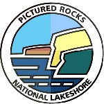 This logo for Pictured Rocks National Lakeshore features colorful cliffs and blue water.