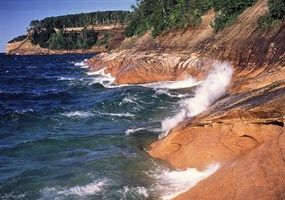 Lake Superior waves splash onto the Pictured Rocks cliffs.