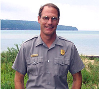 Chris Case, Facility Manager at Pictured Rocks National Lakeshore poses for the camera with Lake Superior in the background.