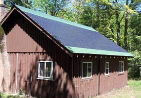 The rustic brown Sullivans Cabin has photovoltaic collector shingles on its roof to power an electric system.