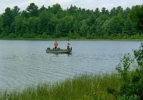 Fisherman in a boat on an inland lake.  They are not wearing personal floatation devices (PDFs), but they should be.