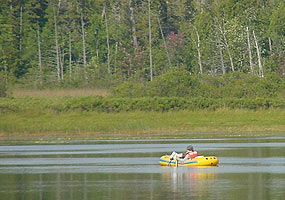 Boaters in a yellow inflatable raft enjoy an afternoon on Little Chapel Lake.