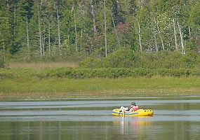 An NPS employee conducting zooplankton and water quality studies while in an inflatable boat on Little Chapel Lake.