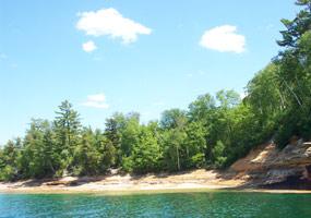 The Lake Superior shoreline near the mouth of the Mosquito River with beautiful blue skies and clear emerald water.