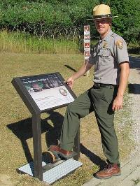 A park ranger using a boot brush station to brush off invasive seeds.