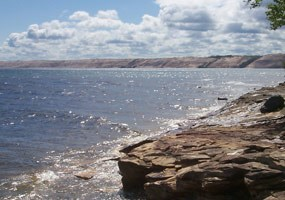 This sandstone shelf lies near Au Sable Point, with the magnificent Grand Sable Dunes rising high above Lake Superior in the background.