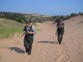 Two members of the invasive plant team hike in the dunes with herbicide in backpack sprayers.