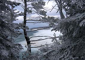 This far-away photo of Miners Beach was taken from the trail to Miners Castle, through snow-covered trees.