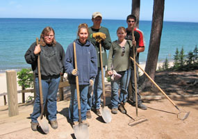 Five Youth Conservation Corps enrollees with their rakes and shovels on the trail above Miners Beach.