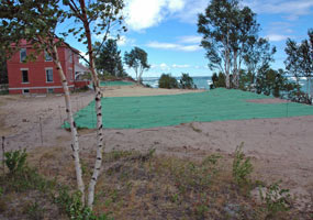 Green stabilization mat covers the ground in front of the red brick head keepers quarters at the Au Sable Light Station. The mat will hold the sand in its place and allow plants to grow.