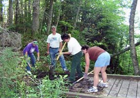 Four Adopt-a-Trail volunteers help maintain a trail and boardwalk.