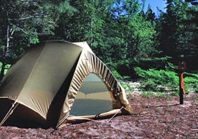 Earth tone brown small tent set up within 15 feet of a numbered post, minimizing visual and ground impact at a backcountry campsite.