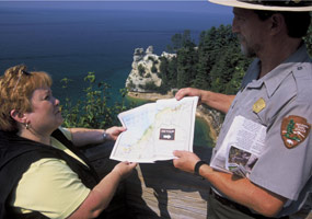 While perusing the park newspaper, a Ranger assists a visitor to Pictured Rocks National Lakeshore.
