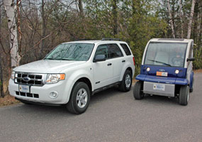 This white Ford Escape SUV is a hybrid vehicle. The smaller Ford Think Neighbor is an electric vehicle.