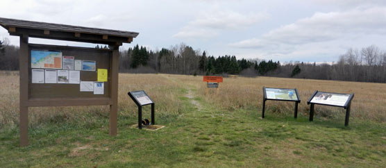 Trailhead at the Grand Sable Visitor Center with its bulletin board, boot brush station & wayside exhibit, trail, backcountry regulations & mileage sign, and set of two North Country National Scenic Trail wayside exhibits.