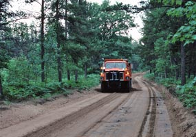 An orange dump truck with grader works on the gravel surface of Alger County Road H-58.