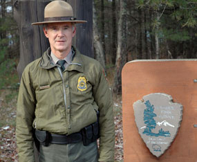 Larry Hach, Chief Ranger at Pictured Rocks National Lakeshore, stands next to the NPS arrowhead.