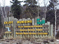 This entrance sign at the City of Munising's boundaries includes a waterfall sketch and rope coil on a vertical log background.