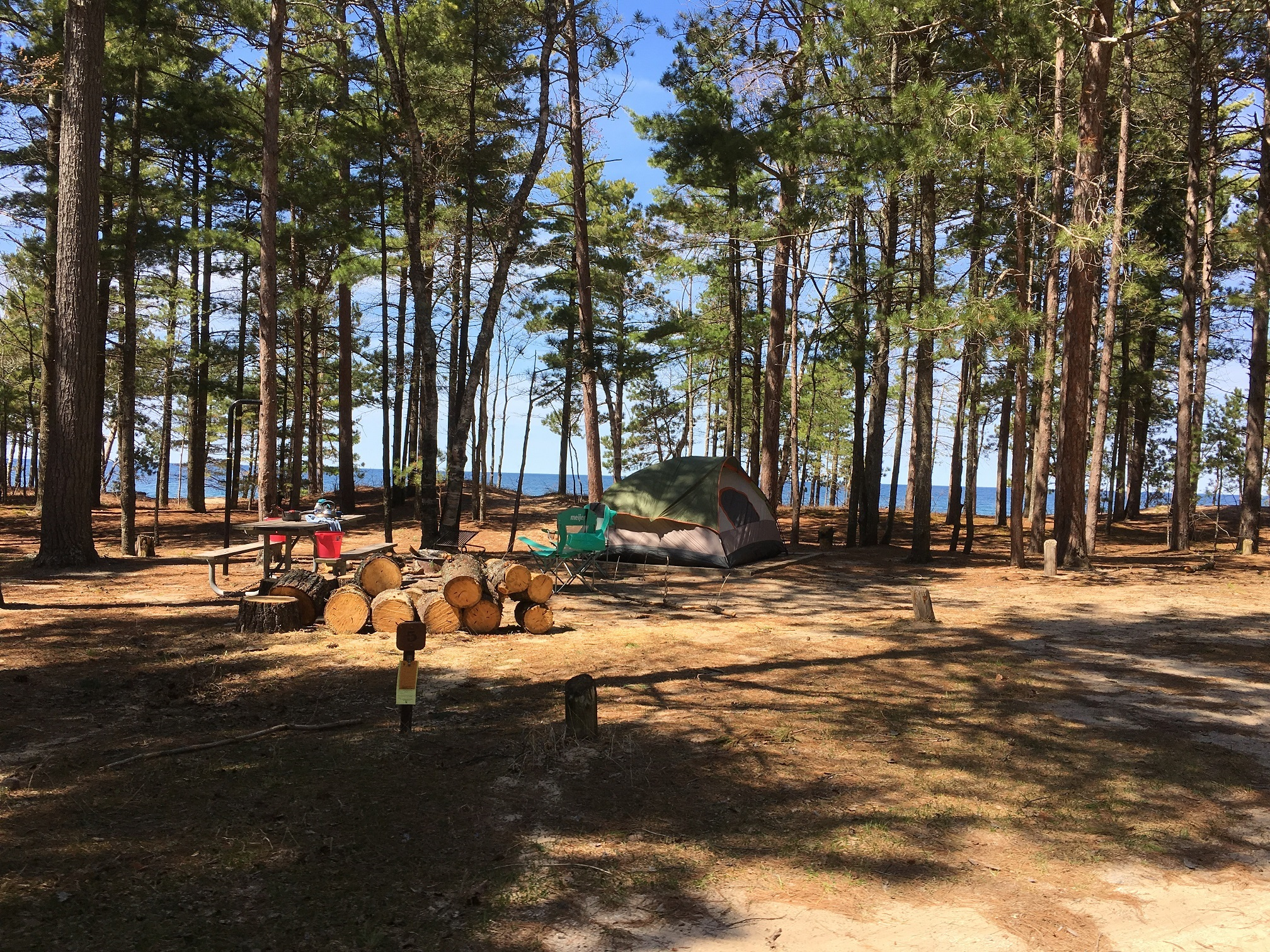Campsite at Twelvemile Beach Campground surrounding by pine trees with Lake Superior in the background. Includes tent, chair, picnic table, and wood pile.