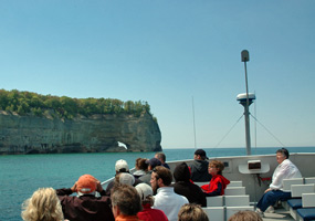 Visitors on Lake Superior boat cruise with Picture Rocks cliffs in background.