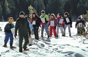 Park Ranger Dave Kronk leads a snowshoe hike with a group of school children.