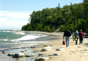 Visitors stroll along Twelvemile Beach as Lake Superior waves roll gently to shore.