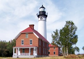Au Sable Light Station stands guard over Lake Superior with its red brick keepers house and white light tower.