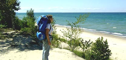 Backpacker standing on beach looking out over Lake Superior