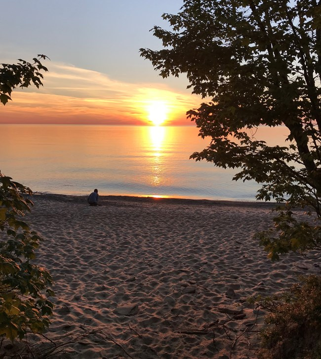 Visitor watching a sunset over Lake Superior at Hurricane River.