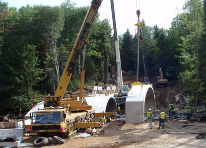 Cranes place a section of con-span for the new Hurricane River Bridge on H-58.