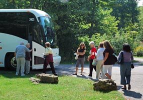A motor coach and passengers at the Miners Castle parking area.