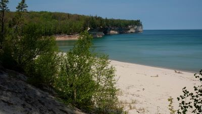 Small beach on Lake Superior. Rock cliffs rise out of the water in the distance. The water is calm.