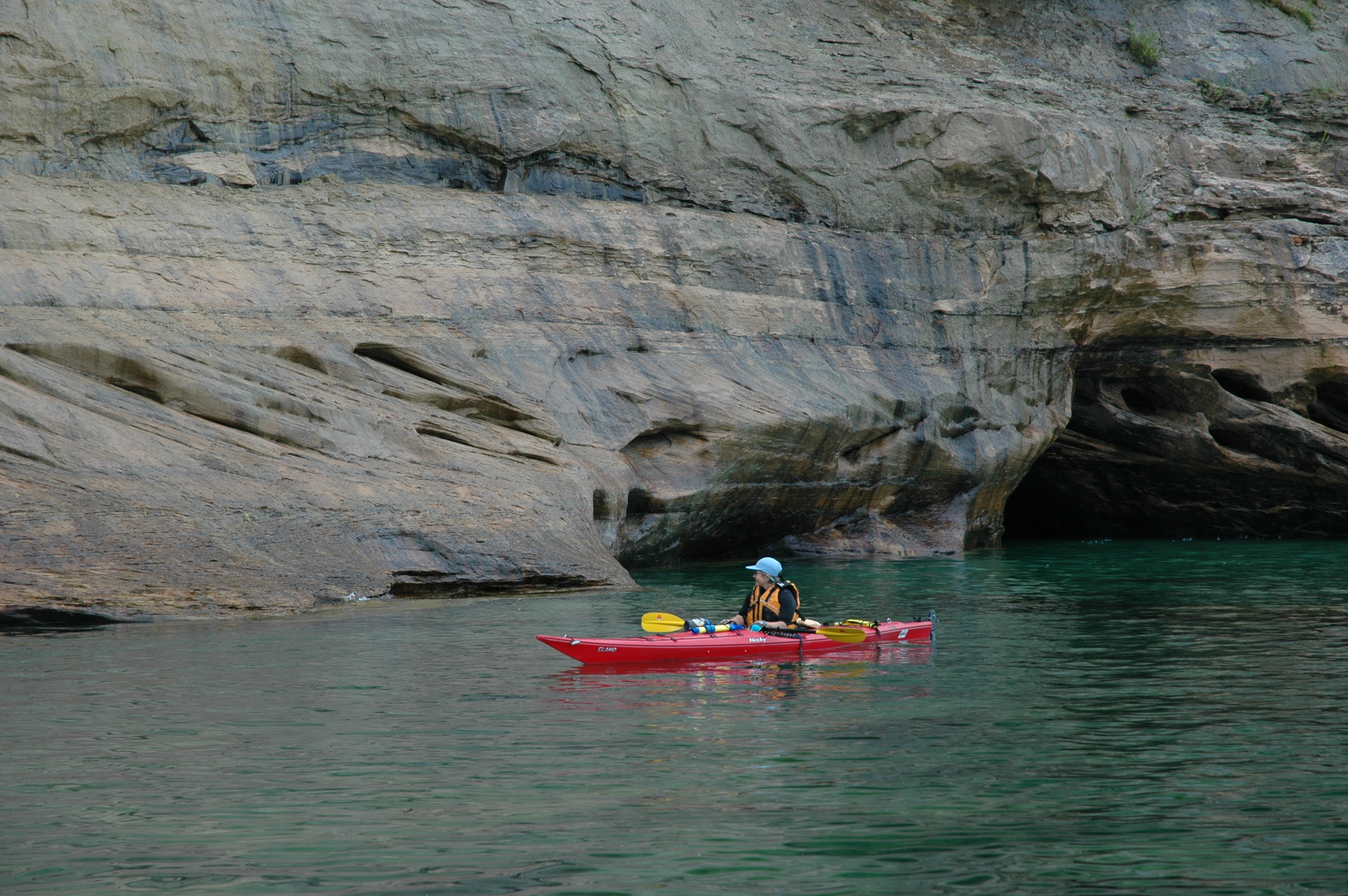Kayaker on Lake Superior along the Pictured Rocks cliffs.